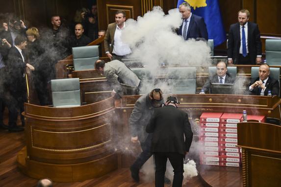 FOTOS DO DIA (Policiais do Kosovo  retiram  bomba de gás lacrimogêneo enquanto a sessão parlamentar é interrompida pela quarta vez. Foto:  AFP PHOTO / Armend NIMANI)