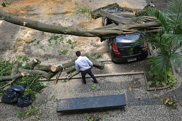 Um homem varre o piso enquanto outros olham para um carro danificado por uma árvore caída depois de uma tempestade no Rio de Janeiro, Brasil, em 7 de fevereiro de 2019.  Foto: CARL DE SOUZA / CDS / AFP. -