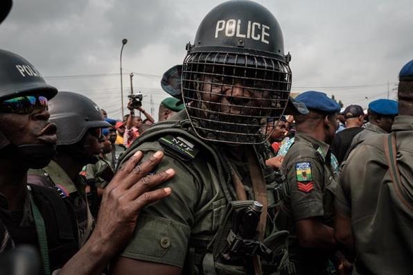Unidade antimotim da polícia nigeriana protege o portão principal do escritório local durante o protesto dos partidários do Congresso Todos Progressistas (APC) em Port Harcourt, no sul da Nigéria. Foto de Yasuyoshi CHIBA / AFP. -