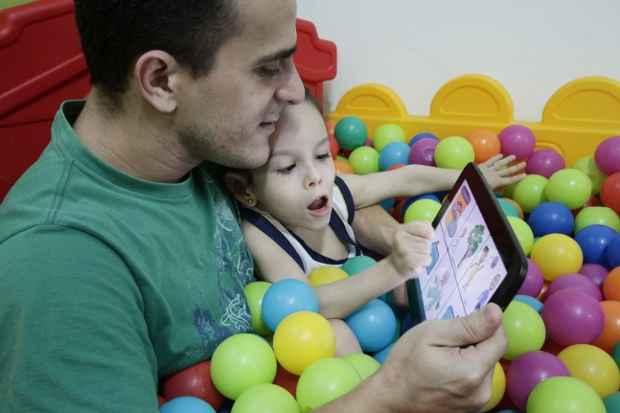 Carlos inventou sistema que permite a Clarinha escolher o que dizer por toque. Ele quer levar invenção a mais crianças. Foto: Alcione Ferreira/DP/D.A Press