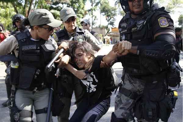 Manifestante � conduzida por policiais: governo teme que os protestos se intensifiquem durante a Copa do Mundo foto: Blenda Souto Maior/DP/D.A Press (Blenda Souto Maior/DP/D.A Press)