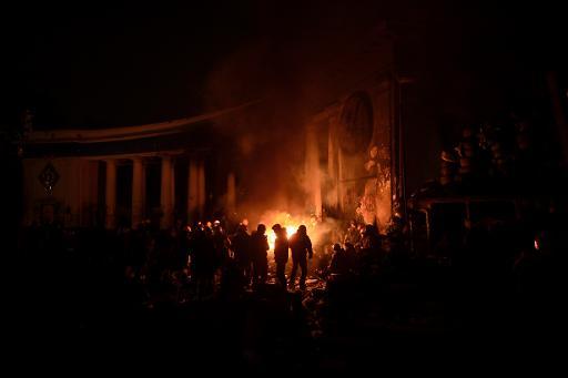 Manifestantes se aquecem em torno de uma fogueira, em uma estrada bloqueada de Kiev Foto: AFP ARIS MESSINIS