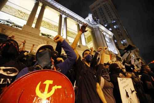 Grupo de black blocs durante protesto no Rio de Janeiro: s�mbolo partid�rio em meio aos mascarados foto: Sergio Moraes/Reuters (Sergio Moraes/Reuters)