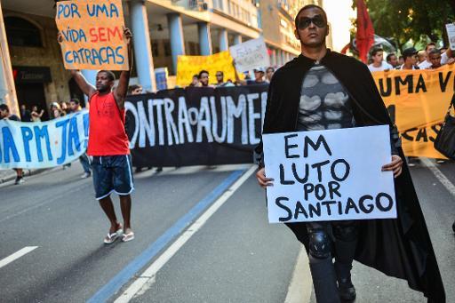 Durante manifesta��o contra aumento das passagens de �nibus no Rio de Janeiro, manifestante exibe cartaz em homenagem ao cinegrafista Santiago Andrade. Foto: Yasuyoshi Chiba/AFP Photo