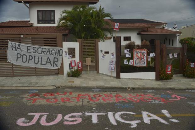 Integrantes de movimentos sociais protestam com faixas, cartazes e picha��es em frente � casa do coronel reformado Carlos Alberto Brilhante Ustra. Foto: Fabio Rodrigues Pozzebom/Ag�ncia Brasil