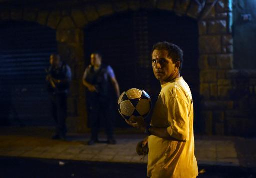 Homem com bola de futebol passa em frente a policiais que montam guarda nas proximidades da favela Pav�o-Pav�ozinho, em Copacabana, durante violentos protestos pela morte de um morador. Foto: Christophe Simon/AFP Photo