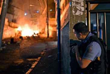 Policial toma posi��o e observa barricada em chamas, durante protesto violento na favela Pav�o-Pav�ozinho, em Copacabana. Foto: Christophe Simon/AFP Photo