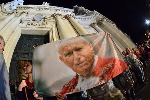 Peregrinos seguram foto de Jo�o Paulo II em Roma no dia 26 de abril de 2014 Giuseppe Cacace/AFP Photo