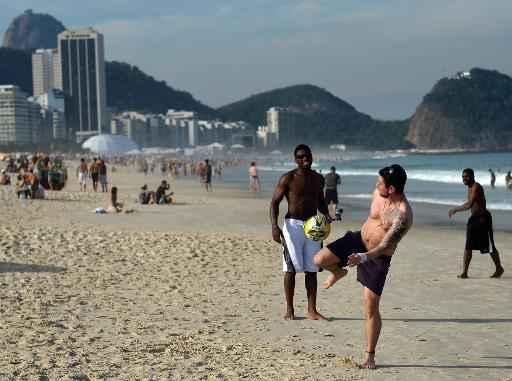 Homens jogam futebol nas areias da praia de Copacabana, no Rio de Janeiro. Foto: Gabriel Bouys/AFP Photo