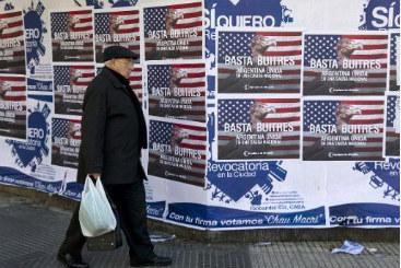 Homem passa em frente a cartazes em rep�dio ao pagamento da d�vida argentina, em Buenos Aires. Foto: � AFP/Alejandro Pagni (Homem passa em frente a cartazes em rep�dio ao pagamento da d�vida argentina, em Buenos Aires. Foto: � AFP/Alejandro Pagni)