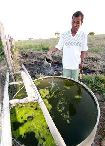 O agricultor Jos� Mendes e a �gua escura extra�da de um dos po�os. Fotos: Solon Queiroz/Esp.EM/D.A. Press