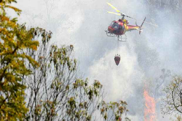 Helic�ptero tenta conter chamas na Serra do Rola-Mo�a: dificuldade de chegar a culpados sobrecarrega respons�veis por combate. Foto: Jair Amaral/EM/D.A press (Jair Amaral/EM/D.A press)