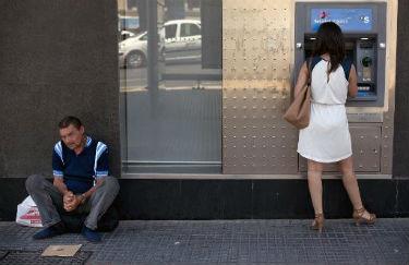 Um homem pede esmolas enquanto uma mulher saca dinheiro na cidade espanhola de M�laga, em 27 de junho de 2014. � AFP/Arquivos Jorge Guerrero