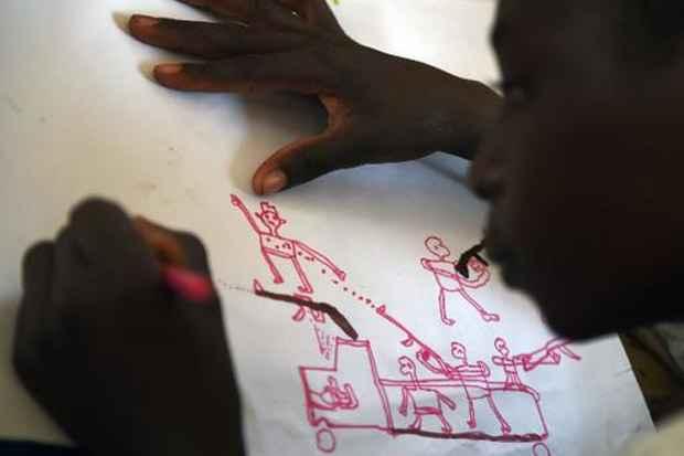 Uma criança nigeriana refugiada desenha cena de ataque durante terapia coordenada pela UNICEF, no campo de refugiados Baga Sola, no dia 6 de abril de 2015. Foto: Philippe Desmazes/AFP/Arquivos