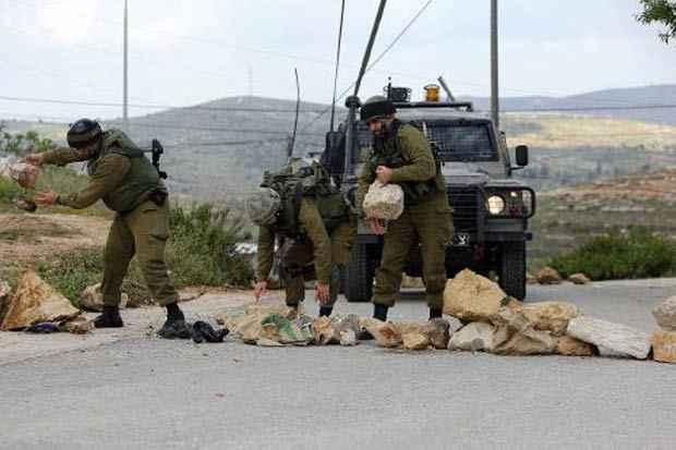 Soldados israelenses retiram pedras durante confrontos com manifestantes palestinos em 13 de abril em Sinjil, na Cisjordânia ocupada. Foto: Abbas Momani/AFP/Arquivos