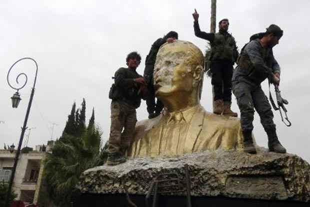 Combatentes da Frente Al-Nosra, braço sírio da Al-Qaeda, atacam estátua do falecido presidente sírio Hafez al-Assad, pai do atual presidente Bashar al-Assad, em Idleb em 28 de março. Foto: Sami Ali/AFP