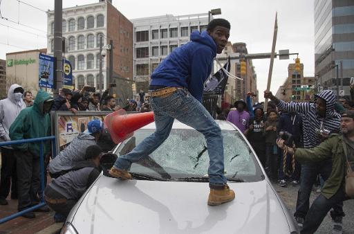 Manifestantes revoltados depredam carro. Foto: AFP Jim Watson