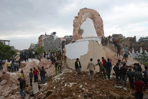 Equipes de resgate e civis observam destroços da torre Dharahara em Katmandu. FOTO: AFP Prakash Mathema