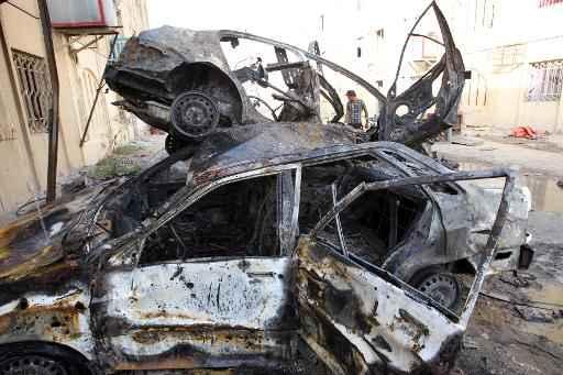 Um homem examina os destroços de carros queimados após atentado-bomba em Bagdá Foto: AFP/Arquivos ALI AL-SAADI