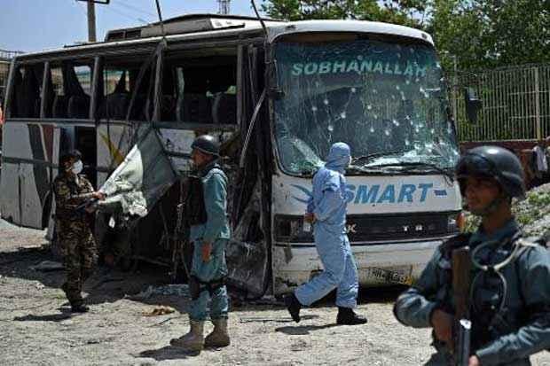 Policiais afegãos inspecionam área de atentado suicida contra ônibus do governo. Foto: Wakil Kohsar/AFP