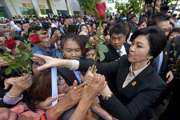 A ex-premier recebe flores de simpatizantes do lado de fora da Suprema Corte. Foto: Pornchai Kittiwongsakul/AFP