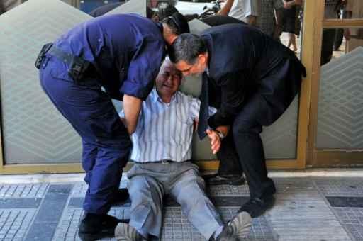 Aposentado grego é ajudado por funcionário de agência bancária e por policial, após passar mal por não conseguir sacar, Tessalônica, 3 de julho de 2015 - Foto: AFP Sakis Mitrolidis  (Foto: AFP Sakis Mitrolidis )