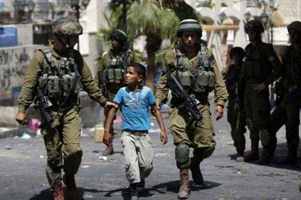 Soldados de Israel prendem um menino palestino após confrontos na cidade de Hebron, Cisjordânia, em junho de 2014. Foto: Thomas Coex/AFP