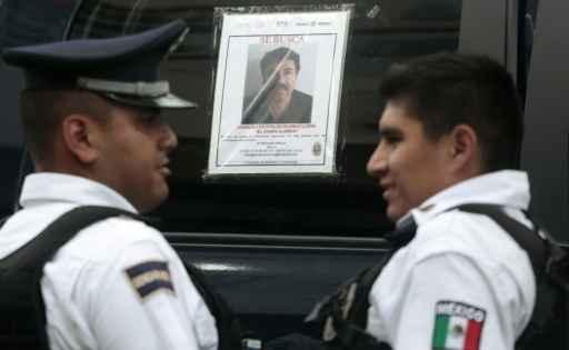 Dois oficiais da Polícia Federal em frente a um carro de patrulha com a foto do fugitivo 'El Chapo' na janela, em Acapulco, no dia 14 de julho de 2015. Foto: Pedro Pardo/ AFP/Arquivos