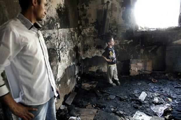Homem e menino palestinos observam a casa onde o bebê morreu, na localidade de Duma. Foto: Thomas Coex/AFP