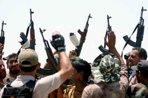 Forças iraquianas e membros da Mobilização Popular levantam suas armas no fronte de combate durante conflito com o Estado Islâmico. Foto: Haidar Mohammed Ali /AFP/Arquivos