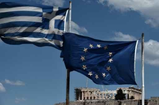 As bandeiras da Grécia (E) e da União Europeia em Atenas. Foto: Aris Messinis/AFP