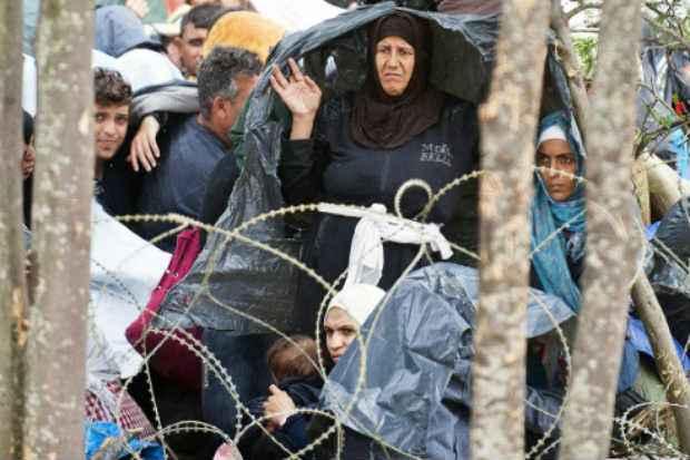 Refugiados se protegem da chuva em uma terra de ninguém entre Macedônia e Grécia, perto de Gevgelija. Foto: AFP Robert Atanasovski