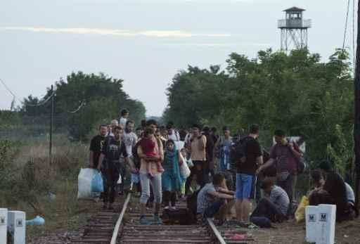 Migrantes caminham por via férrea perto da localidade de Asotthalom, na fronteira entre Hungria e Sérvia. Foto: Csaba Segesvari/AFP