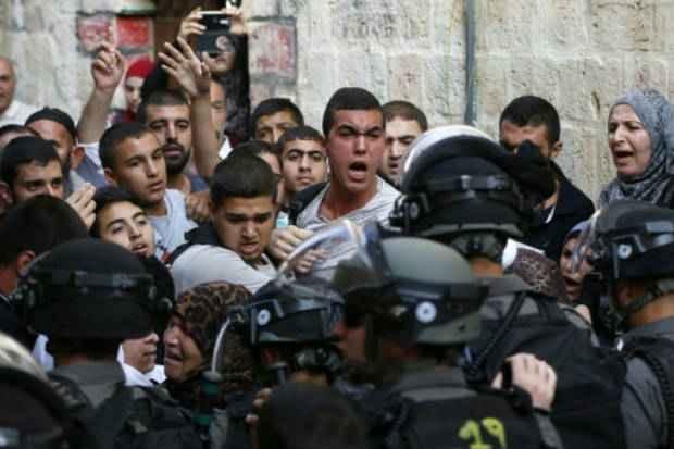Palestinos gritam diante das forças de segurança israelenses, que bloqueavam o caminho para a mesquita de Al-Aqsa, em 13 de setembro de 2015. (Foto: AFP Ahmad Gharabli)
