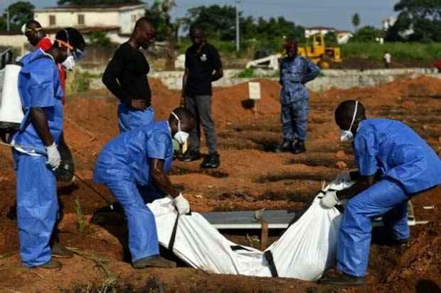 Equipe médica enterra o corpo de uma vítima do Ebola, em Freetown, Serra Leoa, em 2014. Foto: Francisco Leong/AFP