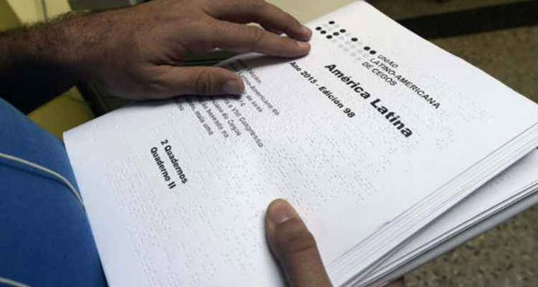 Homem cego lê texto em braile da TifloLibros. Foto: AFP Photo/Arquivo