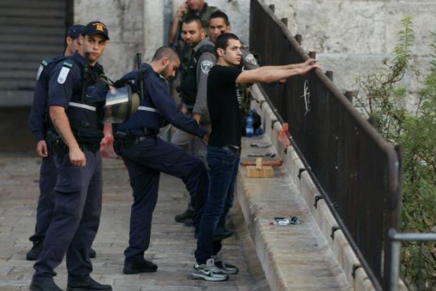 Policiais israelenses revistam palestino, em Jerusalém, no dia 13 de outubro de 2015. Foto: Ahmad Gharabli/AFP