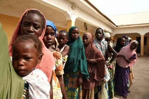 Jovens nigerianas sequestradas pelo Boko Haram e libertadas pelo Exército fazem fila para receber doações de roupas, em um campo de refugiados na cidade de Yola, em maio. Foto: Emmanuel Arewa/AFP