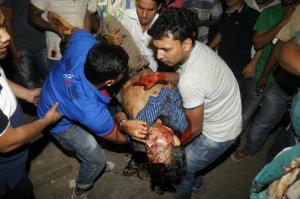 Homens carregam o corpo do editor Faisal Arefin Dipan morto em um ataque em seu escritório. © AFP MUNIR UZ ZAMAN