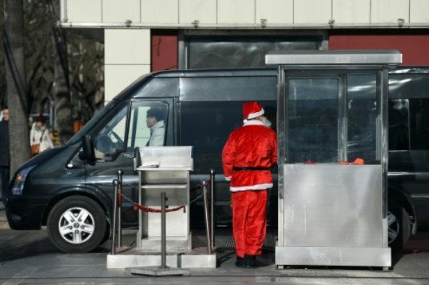 Agente de segurança fantasiado de Papai Noel na entrada de estacionamento de Pequim. Foto: AFP/Arquivos GREG BAKER.