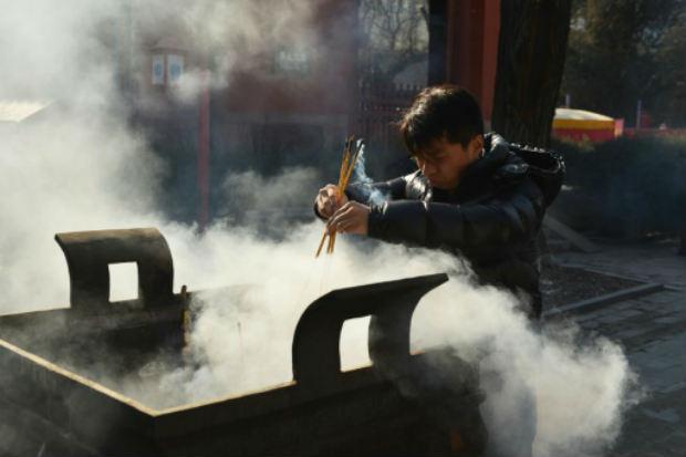 Chinês queima incenso nas comemorações do Ano Novo Lunar, durante o qual aconteceu o episódio com o bebê que reviveu. Foto: AFP GREG BAKER