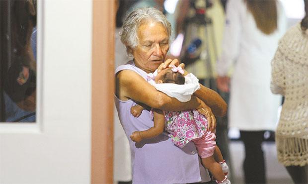 A avó Josefa Valdemar segura a neta que tem microcefalia e dá apoio à filha para superar as dificuldades. Foto: Julio Jacobina/ DP