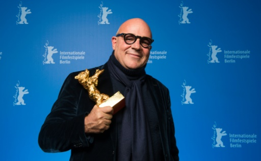 """O cineasta italiano Gianfranco Rosi posa com o Urso de Ouro pelo filme """"Fuocoammare"""". Foto: Bernd Von Jutrczenka/POOL/AFP"""