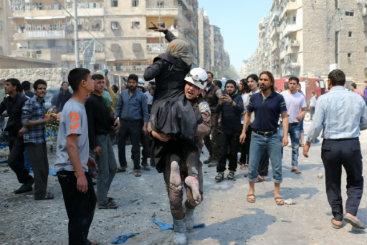 Funcionário da defesa civil evacua uma mulher após borbardeios no bairro de Treeq al-Bab. Crédito: Ameer Alhalbi/AFP
