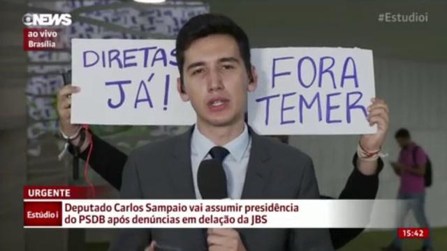 Homem segura cartazes durante passagem ao vivo da GloboNews. Foto: Twitter/Reprodução