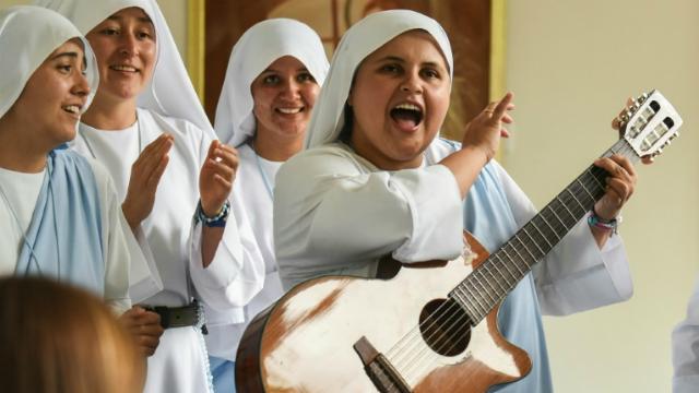 A freira Maria Valentina de los Ángeles, toca violão e canta junto a outras freiras nas proximidades de Cali, Colômbia. Foto: Luis Robayo/AFP