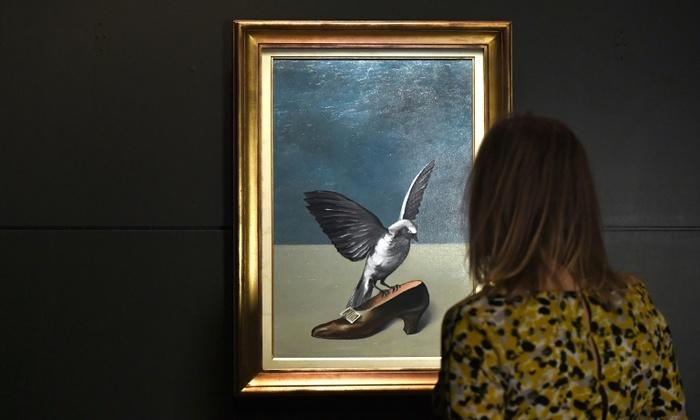 """Mulher observa quadro """"Dieu n'est pas un saint"""", do artista René Magritte, em Bruxelas, em 14 de novembro de 2017. Foto: Arquivo/AFP"""