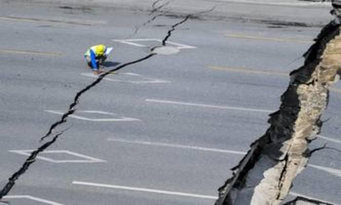 Investigador inspeciona local onde uma estrada afundou. Foto: AFP