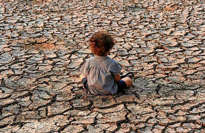 Criança nos arredores de Tegucigalpa, Honduras: exploração desmedida do solo e mudanças climáticas vão impactar a produção de alimentos. Foto: Orlando Sierra/AFP