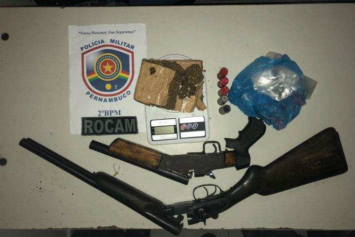 Foram encontradas duas espingardas calibre 12, munições, 750g de maconha prensada, 8g de crack e uma balança de precisão. Foto: Polícia Militar/Divulgação